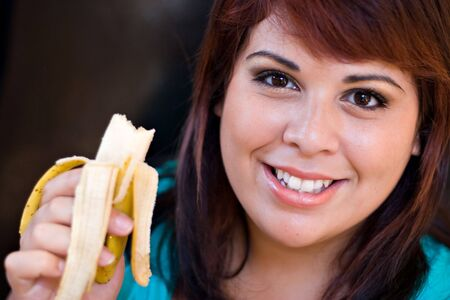 A young woman happily eating a banana.  Shallow depth of field with stronger focus on the face. Stock Photo - 5495188