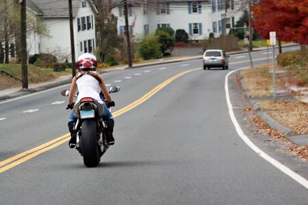 A young woman on a motorcycle maintains a safe following distance with the car ahead.