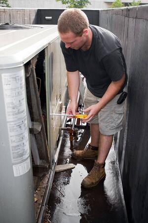 aire acondicionado: Un t�cnico de HVAC j�venes que trabajan en un sistema a�reo comercial en la azotea.