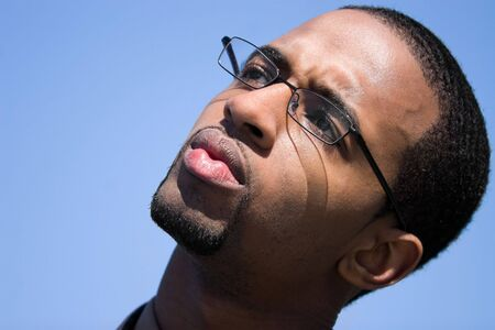 contemplative: A contemplative African American man wearing glasses isolated over a blue background.  Stock Photo