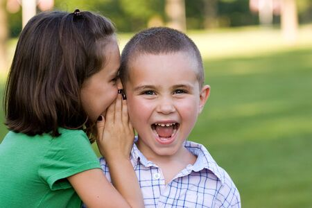 A young girl telling her brother a secret. photo