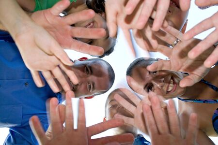 A happy family posing in a group huddle formation and waving at the camera.  Intentional motion blur of the hands. Stock Photo - 5555552