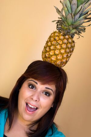 A young woman with a funny expression balancing a pineapple on her head. photo