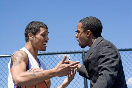 A young basketball player getting yelled at by his coach.