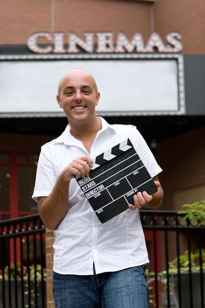 critic: A young man or movie critic holding a movie directors clap board in front of the cinemas.