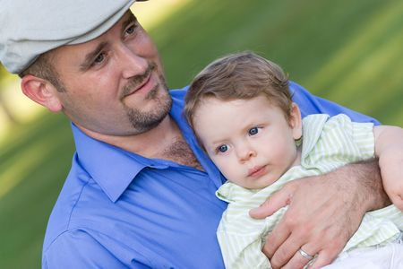 A proud young father holding his cute baby boy with a smile on his face. Stock Photo - 5654057