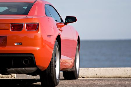 rear wheel: A modern sports car parked at the beach.