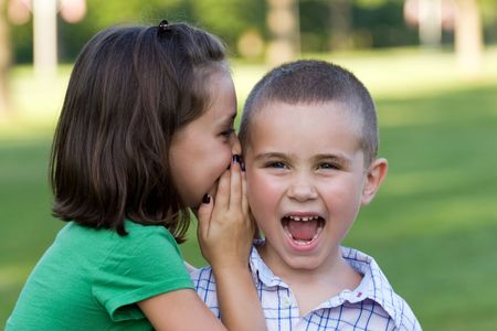 goofing: A young girl telling her brother a secret.