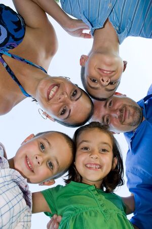 huddle: A happy family posing in a group huddle formation. Stock Photo