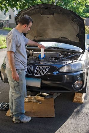 A young man adding oil to his car at the end of an oil change. photo
