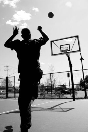 Silhouette of a basketball player shooting the ball at the basket. photo