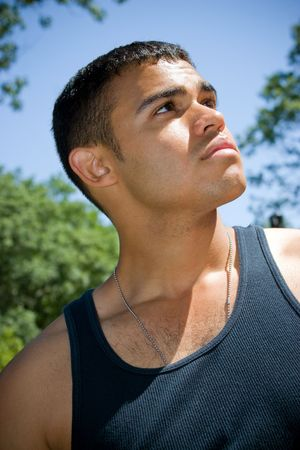 A serious young man wearing dog tags around his neck outdoors. photo