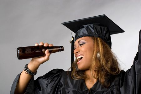 graduation party: A recent graduate posing in her cap and gown holding beer bottle isolated over a silver background.