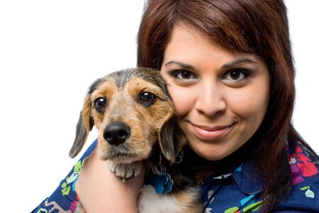 beagle mix: A young woman holding her cute mixed breed puppy isolated on a white background. The dog is half beagle and half yorkshire terrier. Stock Photo