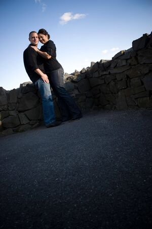 A young happy couple in a loving embrace outdoors with copy space. Imagens
