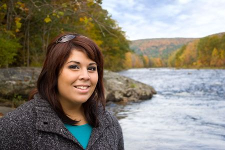A young plus sized model posing by a river in New England during Autumn. photo