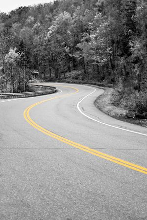 A curved New England road with selective isolated color and the center double lines in yellow. photo