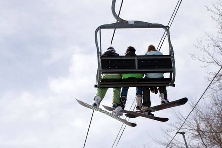 boarders: Three snowboarder friends ride the ski lift to the top of the mountain. Stock Photo
