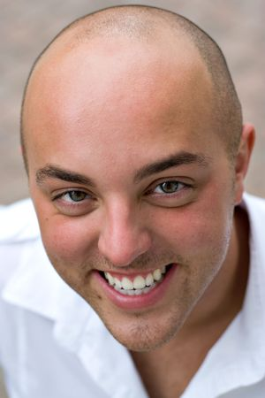 A smiling young bald man up close.  Shallow depth of field. photo