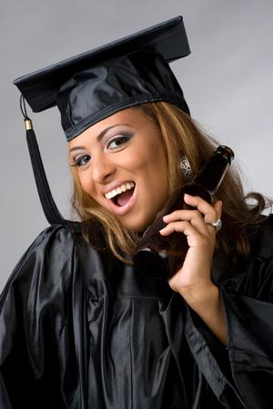 A recent graduate posing in her cap and gown holding beer bottle isolated over a silver background. photo