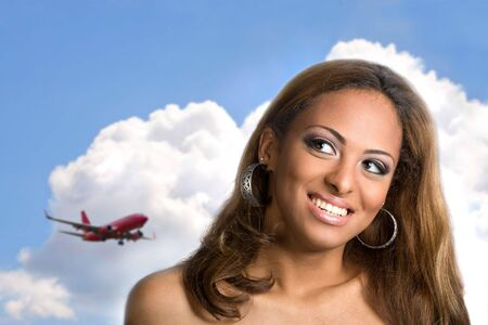 anticipating: A young woman with a big smile on her face thinking about traveling or taking a vacation to an exotic place.