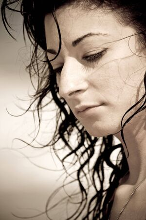 A young woman with wet hair by the sea.  Sepia tone.