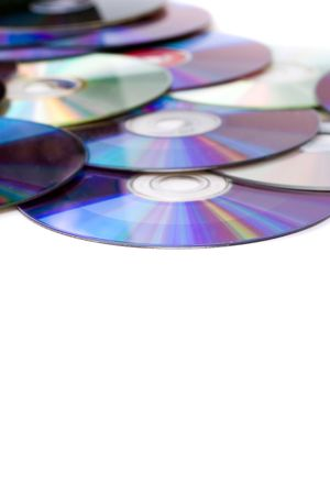 pirated: Blank dvd disks scatted over a white background. Shallow depth of field.