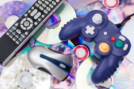 Remote control wireless computer mouse and video game controller over a bed of dvd disks isolated over white. Stock Photo