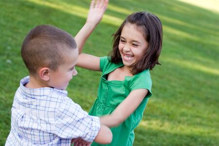 hits: A little girl swings her arms at her brother as they rough house playfully.  Slight motion blur on the arms.