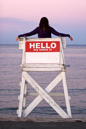 relaxes: Una mujer se relaja en una silla vacante salvavidas cuando el signo en la parte trasera dice HOLA MI NOMBRE ES.