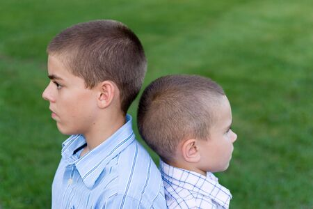 Two young boys sitting back to back outdoors.   photo