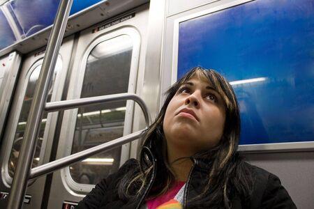 mirada triste: Una mujer joven con una mirada triste en su cara de caballo en el metro. Foto de archivo