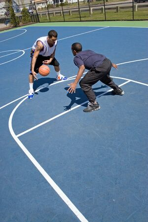 A young basketball player guarding his opponent during a one on one basketball game. photo