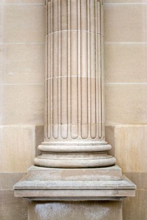 An old stone column on the exterior of a building. photo