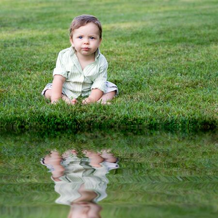 babies: Cute young infant sitting in the grass all alone.