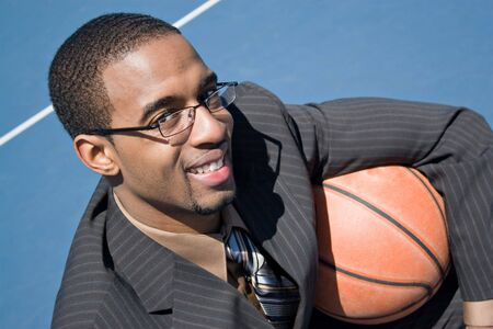 African American man in a business suit posing with a basketball.  He could be a coach player recruiter scout or trainer. photo