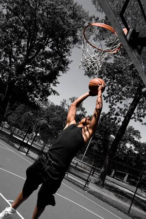 A young man driving to the basketball hoop for a dunk with selective color. photo