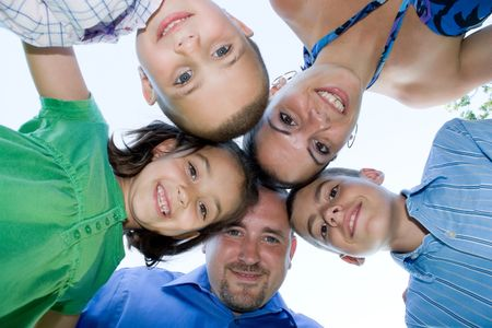 smiles: A happy family posing in a group huddle formation. Stock Photo