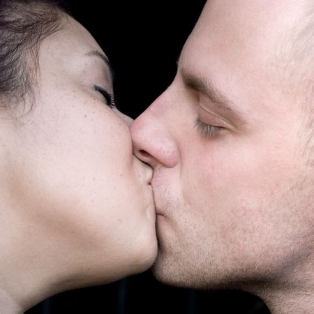 at each other: A young couple kissing each other.