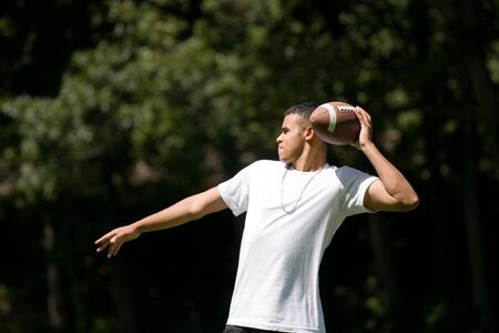 A young adult throwing a football outside. photo