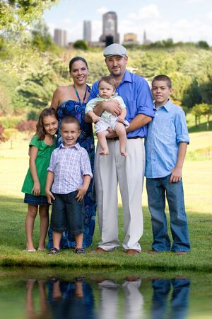 Portrait of an attractive young family with four children posing in a park outside of the city. Stock Photo - 5968091