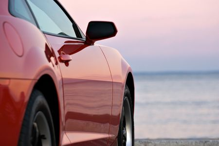 rear wheel: A modern sports car parked at the beach around sunset.