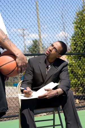 A confident coach speaking to one of his players on the basketball team. photo