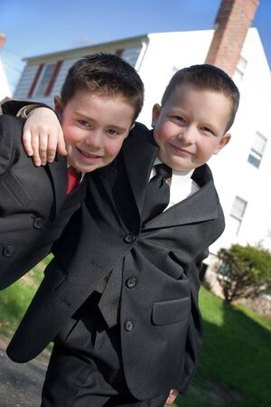 brotherly love: Two happy young boys dressed in suits with smiles on their faces.