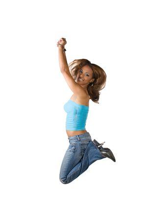 knees bent: Una giovane donna Latina saltare in aria con il suo ginocchia piegate isolata su uno sfondo bianco. Archivio Fotografico