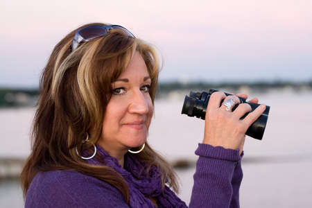 highlighted hair: A woman looking with binoculars at the beach. Stock Photo