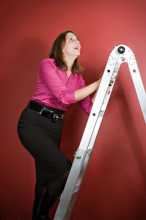 A young woman climbs a ladder over a red background. Фото со стока