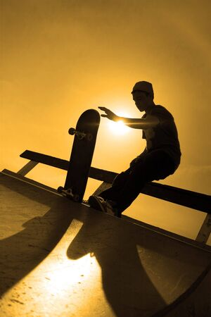 on ramp: A silhouette of a young skateboarder at the top of a ramp at the skate park.