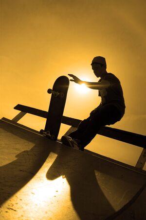 ni�o en patines: Una silueta de un joven skater en la parte superior de una rampa en el Parque de skate. Foto de archivo
