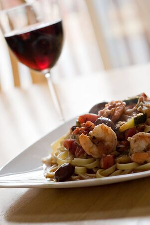 A delicious shrimp and pasta dish along with a glass of red wine. Shallow depth of field. photo
